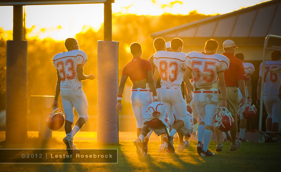 Football players walk off the field after a football game at sunset