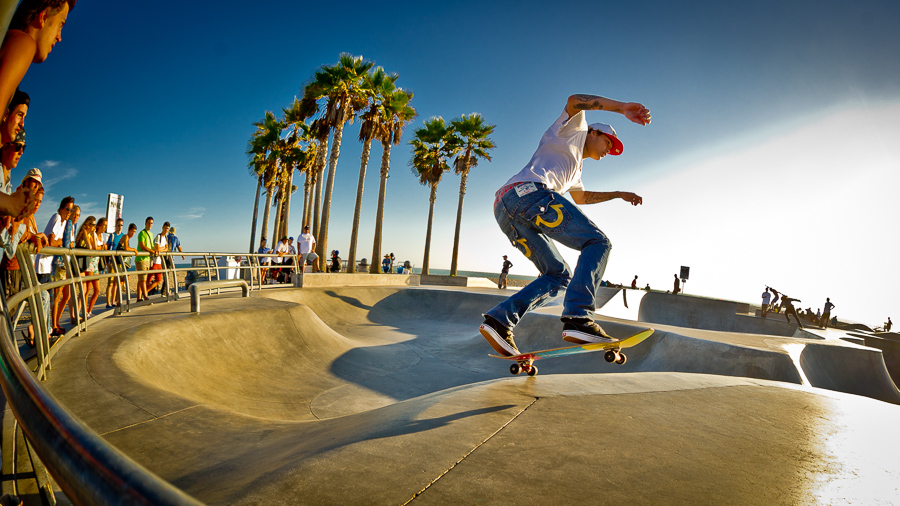 Skateboarder practicing his board skills at Venice Beach.