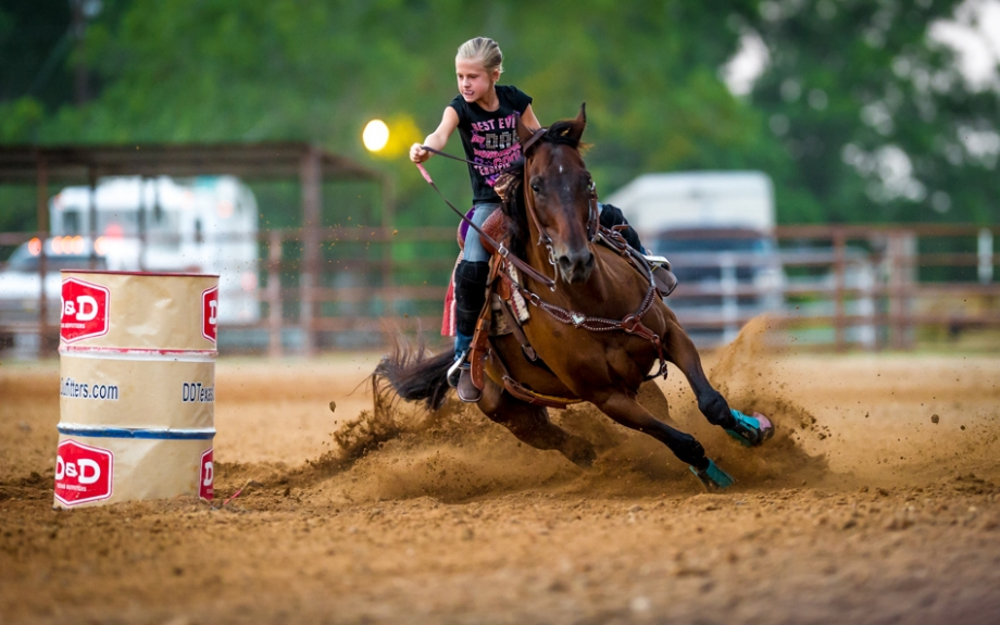 A young rider navigates her horse around a barrel during the Barrel Racing Series held at Rio Cibolo Ranch in Marion, Texas.  It takes a bond between a horse and rider to be successful in barrel racing.