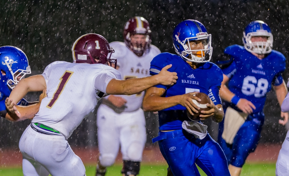 Bandera quarterback, Joe Rodriguez attempts to elude Andy Griffes of San Antonio Christian during a wet game in Bandera.  SACS went on to win the game 28 - 0.  Click here to see more photos.
