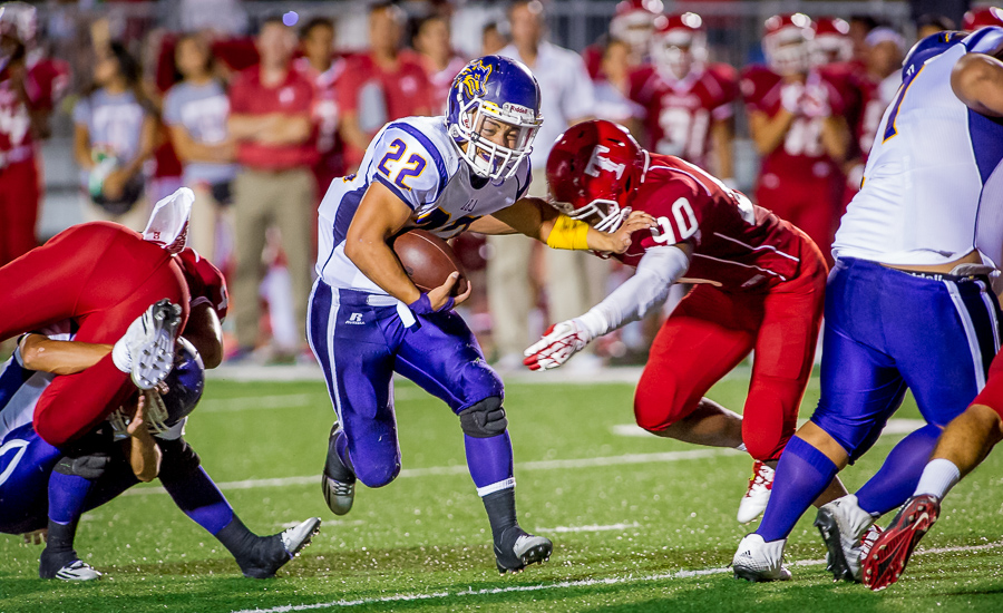 Laredo LBJ running back #22 Juan Cisneros, pushes his way past Taft defensive end Brian Ukaegbu during a game at Gustafson stadium.  Taft held on to win 21-14.